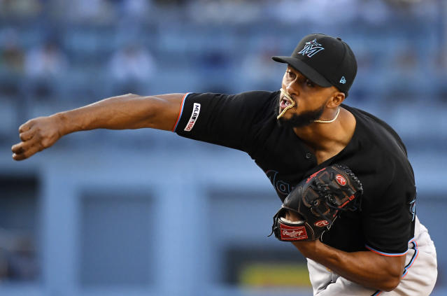 Miami Marlins starting pitcher Sandy Alcantara gets his chain around his mouth as he throws to the plate during the first inning of a baseball game against the Los Angeles Dodgers Saturday, July 20, 2019, in Los Angeles. (AP Photo/Mark J. Terrill)