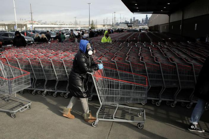 Dee Jackson wears a gas mask as she and other shoppers line up before opening at a Costco store, following reports of coronavirus disease (COVID-19) cases in the country, in Seattle