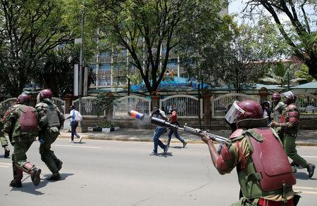 A riot policeman fires tear gas to disperse supporters of Kenyan opposition National Super Alliance (NASA) coalition, during a protest along a street in Nairobi, Kenya October 16, 2017. REUTERS/Thomas Mukoya