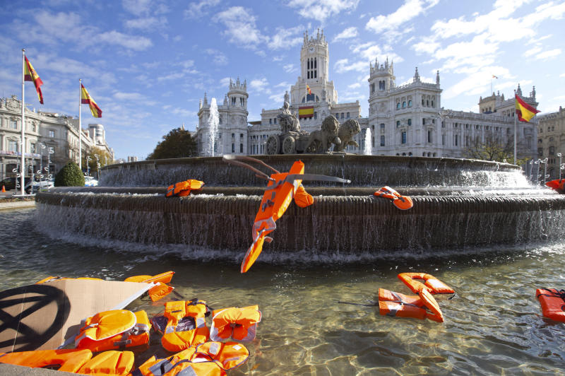 "Lifejackets are thrown into the Cibeles fountain during a protest performance in Madrid, Spain, Tuesday, Dec. 3, 2019. Some 20 activists from the international group called Extinction Rebellion cut off traffic in central Madrid and staged a brief theatrical performance to protest the climate crisis. The activists held up a banner in Russian that read ""Climate Crisis. To speak the truth. To take action immediately."" Some 10 others dressed in red robes and with their faces whitened to symbolize the human species' peril danced briefly before police moved in to end the protest. (AP Photo/Paul White)"