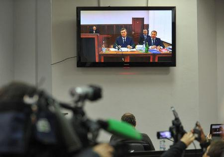 Ukraine's former President Viktor Yanukovich is seen on the screen as he comes to give evidence to a Ukrainian court via a video link, appearing as a witness in the trial of former riot police force members suspected of killing participants of the 2014 anti-government and pro-European Union mass protests, inside a building of a regional court in Rostov-on-Don, Russia, November 25, 2016. REUTERS/Sergei Pivovarov