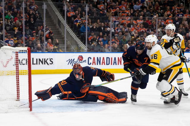 Edmonton Oilers goaltender Mike Smith (41) can't make the save on a goal by Pittsburgh Penguins' Joseph Blandisi as Penguins' Zach Aston-Reese (46), who had an assist, watches during the first period of an NHL hockey game Friday, Dec. 20, 2019, in Edmonton, Alberta. (Codie McLachlan/The Canadian Press via AP)