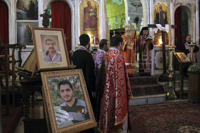 Portraits of two men are on display as people pray for three Christian men killed by gunmen in the predominately Christian village of Maaloula during a service at the al-Zaytoun Roman Catholic Church, Damascus, Syria, September 14, 2013. Government troops are battling for the ancient Christian village of Maaloula northeast of the capital of Damascus that was a major tourist attraction before the civil war. (AP Photo)