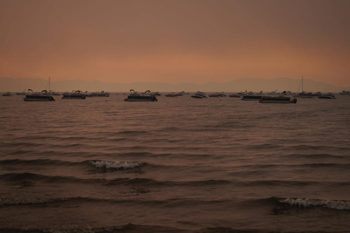 FILE - In this Aug. 31, 2021 file photo boats float in the water away from a dock in South Lake Tahoe, Calif., as the Caldor Fire approaches Lake Tahoe. With wildfire no longer threatening Lake Tahoe, residents, tourists and scientists drawn to its clean alpine air, clear blue waters and fragrant pine trees now wonder about the long-term effects that will remain after wildfire season ends. (AP Photo/Jae C. Hong,File)