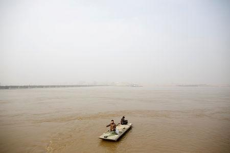 FILE PHOTO: Fishermen travel down the Yellow River to cast their net on the northern outskirts of Zhengzhou, Henan province, China, February 21, 2019. REUTERS/Thomas Peter/File Photo