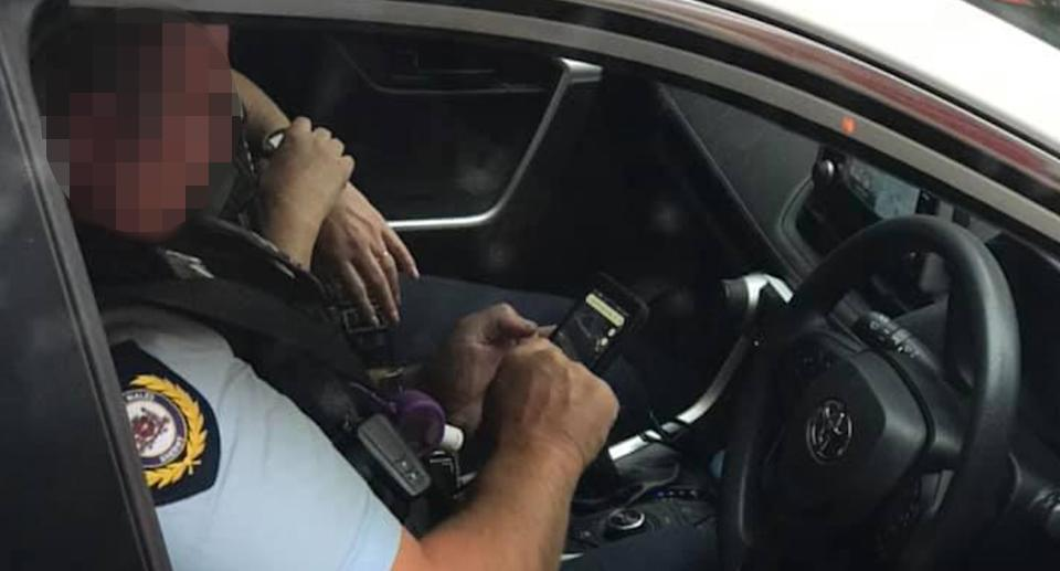 This sheriff was spotted using a mobile phone while behind the wheel of a car stopped at traffic lights.