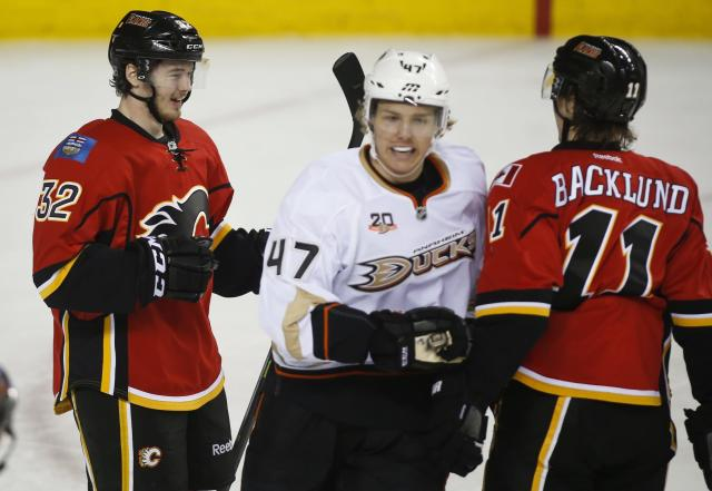 Anaheim Ducks' Hampus Lindholm, center, from Sweden, skates past Calgary Flames' Paul Byron, left, celebrating his goal with teammate Mikael Backlund, from Sweden, during the first period of an NHL hockey game in Calgary, Alberta, Wednesday, March 12, 2014. (AP Photo/The Canadian Press, Jeff McIntosh)