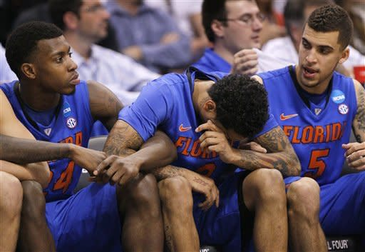Florida players sit in the closing moments of the second half of an NCAA tournament West Regional final college basketball game against Louisville, Saturday, March 24, 2012, in Phoenix. Florida lost to Louisville 72-68. (AP Photo/Matt York)