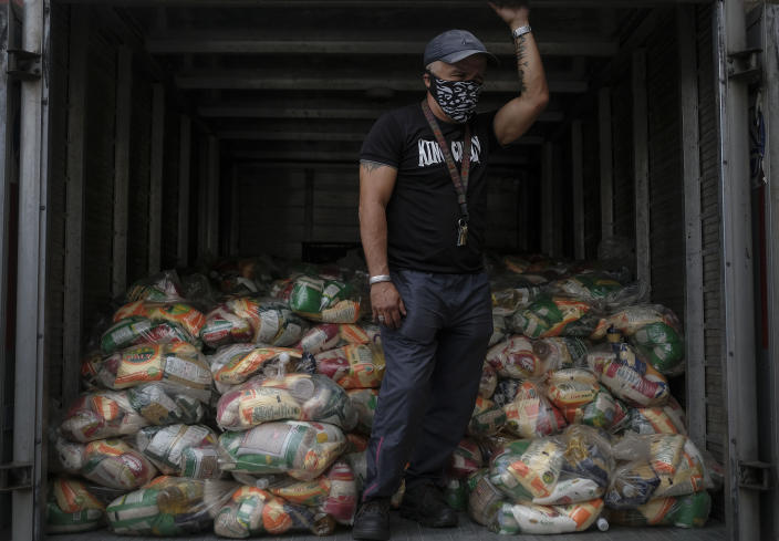A man waits to unload bags of basic food staples, such as pasta, sugar, flour and kitchen oil, provided by a government food assistance program, in the Santa Rosalia neighborhood of Caracas, Venezuela, Saturday, April 10, 2021. The program known as Local Committees of Supply and Production, CLAP, provides subsidized food for vulnerable families, especially now in the midst of a quarantine to stop the COVID-19 pandemic that has left many without income. (AP Photo/Matias Delacroix)