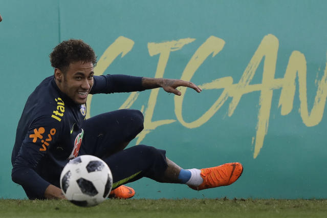 Brazil's Neymar smiles after taking a spill on the pitch during a national soccer team practice session ahead the World Cup in Russia, at the Granja Comary training center In Teresopolis, Brazil, Friday, May 25, 2018. Neymar, the worlds highest paid soccer player, is nearly recovered from a foot operation and has joined 16 of his teammates in Teresopolis, looking ahead to competing in Russia at the World Cup in July. (AP Photo/Leo Correa)