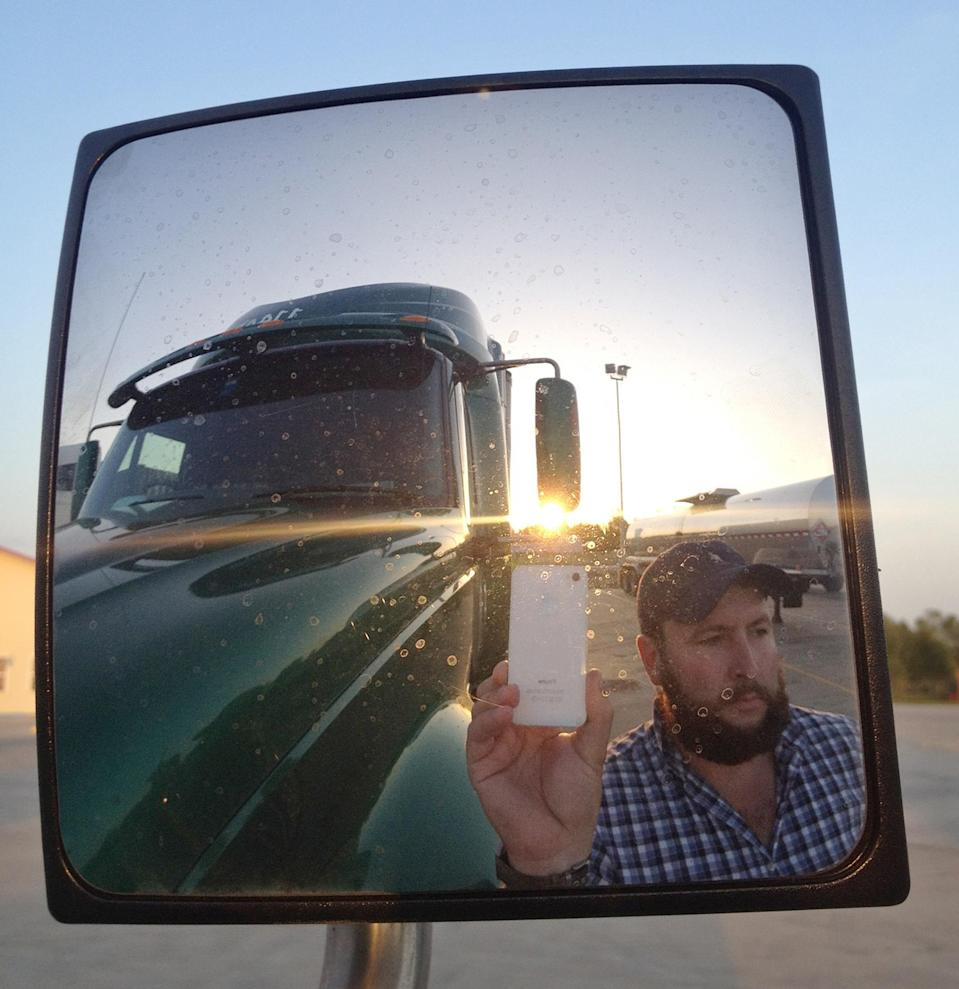 "This undated image provided by James Weitze shows a truck driver taking a self portrait on the road. Weitze satisfies his video fix with an iPhone. He sleeps most of the time in his truck, and has no apartment. To be sure, he's an extreme case and probably wouldn't fit into Nielsen's definition of a household in the first place. But he's watching Netflix enough to keep up on shows like ""Weeds,"" ""30 Rock,"" ""Arrested Development,"" ""Breaking Bad,"" ""It's Always Sunny in Philadelphia"" and ""Sons of Anarchy."" (AP Photo/James Weitze)"