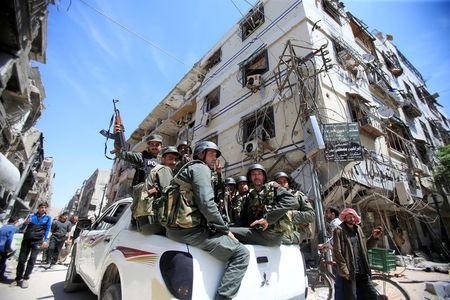Members of the Syrian police hold their weapons as they sit on a back of a truck at the city of Douma, Damascus