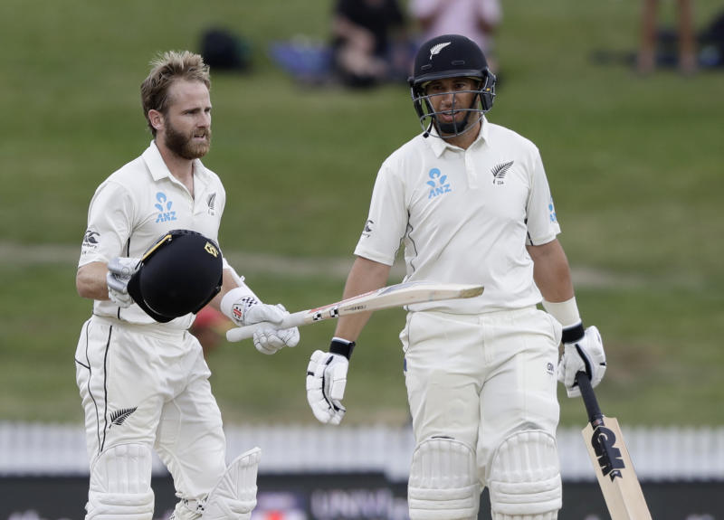 New Zealand's Kane Williamson, left, reacts after scoring a century as teammate Ross Taylor looks on during play on the final day of the second cricket test between England and New Zealand at Seddon Park in Hamilton, New Zealand, Tuesday, Dec. 3, 2019. (AP Photo/Mark Baker)