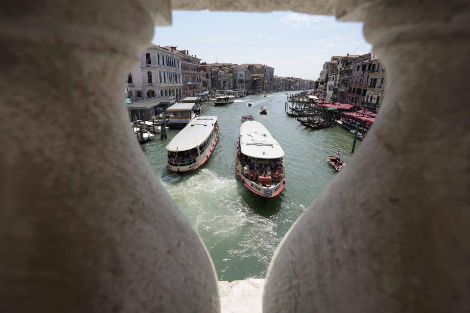 Public transport boats carrying tourists and citizens navigate along the Grand Canal, in Venice, Italy, Thursday, June 17, 2021. After a 15-month pause in mass international travel, Venetians are contemplating how to welcome visitors back to the picture-postcard canals and Byzantine backdrops without suffering the indignities of crowds clogging its narrow alleyways, day-trippers perched on stoops to imbibe a panino and hordes of selfie-takers straining for a spot on the Rialto Bridge or in front of St. Mark's Basilica. (AP Photo/Luca Bruno)