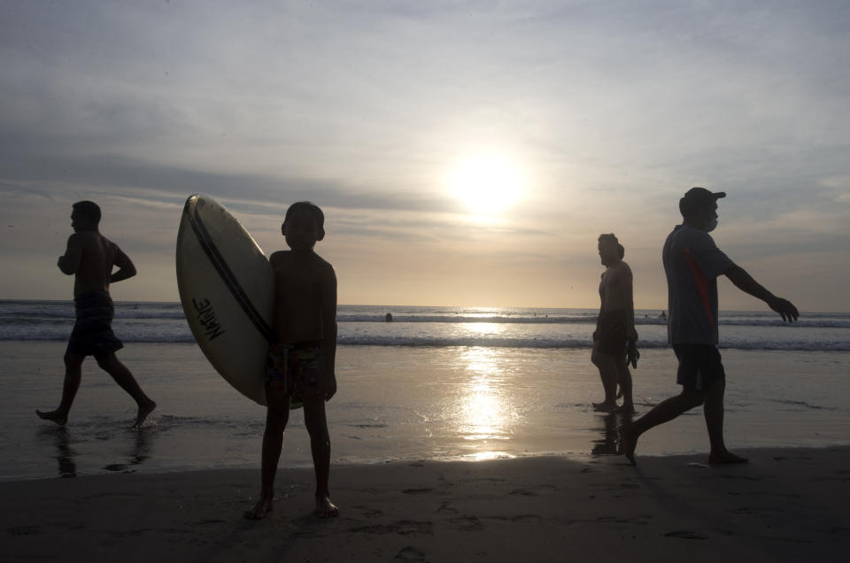People walk on beach during a sunset at Kuta beach, Bali, Indonesia on Thursday, Oct. 14, 2021. The Indonesian resort island of Bali welcomed international travelers to its shops and white-sand beaches for the first time in more than a year Thursday - if they're vaccinated, test negative, hail from certain countries, quarantine and heed restrictions in public. (AP Photo/Firdia Lisnawati)