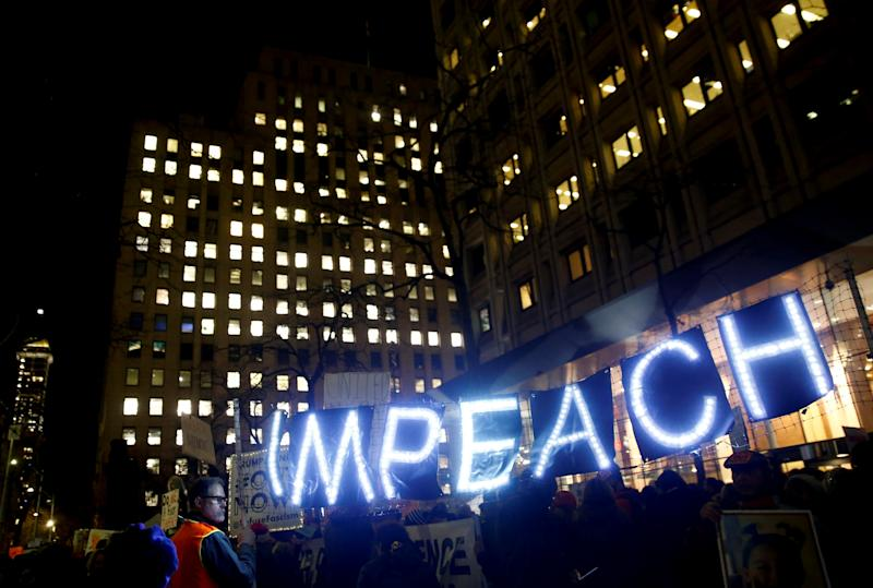"""Protesters hold a lit-up """"impeach"""" sign as they take part in a rally to support the impeachment and removal of U.S. President Donald Trump outside the federal building in Seattle, Washington, U.S. December 17, 2019. REUTERS/Lindsey Wasson TPX IMAGES OF THE DAY"""
