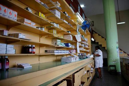 An employee talks on the phone inside a pharmacy in Havana, Cuba, December 1, 2017. REUTERS/Alexandre Meneghini