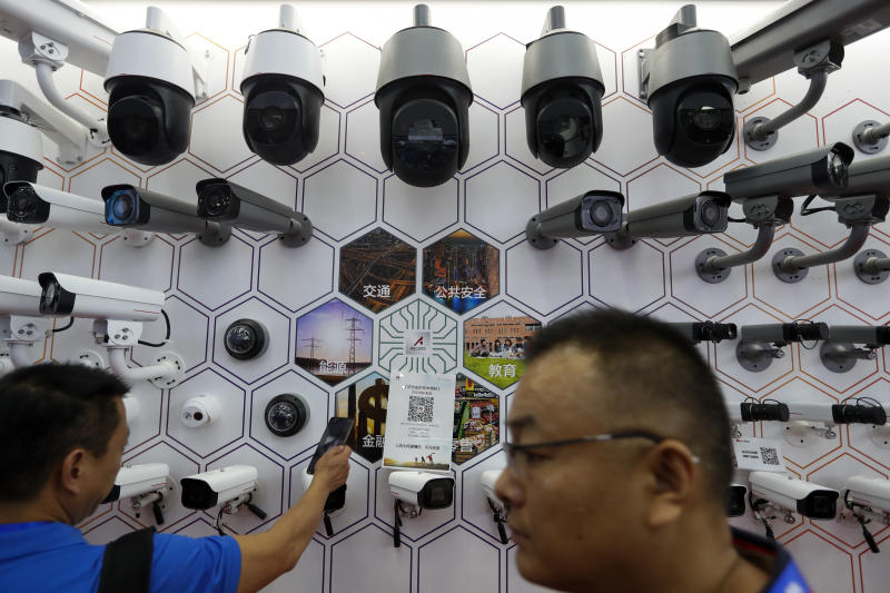 FILE - In this Oct. 29, 2019, file photo visitors look at the surveillance cameras by China's telecoms equipment giant Huawei on display at the China Public Security Expo in Shenzhen, China's Guangdong province. A federal judge in Texas has dismissed Chinese tech giant Huawei's lawsuit challenging a U.S. law that bars the government and its contractors from using Huawei equipment because of security concerns. (AP Photo/Andy Wong, File)