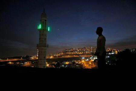 A man stands near a mosque opposite to a neighborhood in east Jerusalem