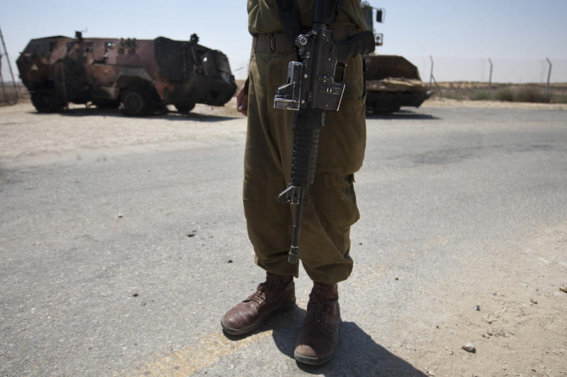 """An Israeli soldier examines the wreckage of an Egyptian military vehicle after militants burst it through a security fence into Israel from Egypt, at an Israeli military base along the border with Egypt, southern Israel, Monday, Aug. 6, 2012. Masked gunmen killed 16 Egyptian soldiers on Sunday, Aug. 5, 2012, at a checkpoint along the border with Gaza and Israel, the first such attack on troops and then the attackers drove off, crashing into Israel, officials said. Egypt blamed Islamist militants from Gaza and Egypt's troubled Sinai Peninsula. President Mohammed Morsi said the attackers """"will pay dearly."""" The Israeli military said the attack was part of a plot to abduct an Israeli soldier, and two vehicles commandeered by the attackers crashed into Israel, where one blew up. (AP Photo/Ariel Schalit)"""