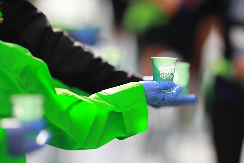 A volunteers holds out a cup of water during the 2019 New York City Marathon. (Photo: Gordon Donovan/Yahoo News)