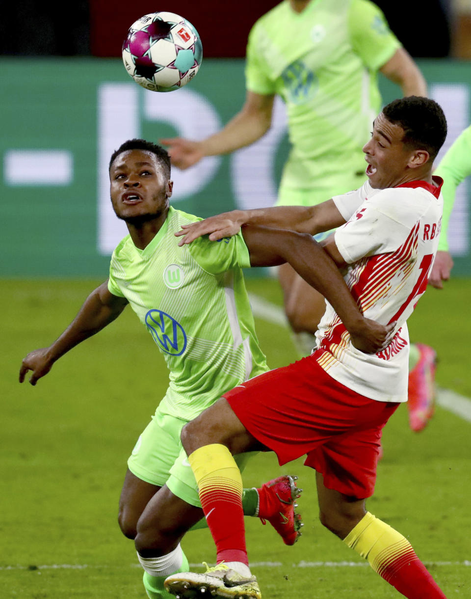 Wolfsburg's Bote Baku, left, and Leipzig's Tyler Adams, right, challenge for the ball during the German soccer cup, DFB Pokal, quarter final match between RB Leipzig and VfL Wolfsburg in Leipzig, Germany, Wednesday, March 3, 2021. (AP Photo/Michael Sohn)