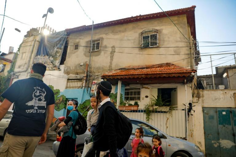 Israeli settlers walk in front of a home inhabited by Palestinians, in the predominantly Arab neighbourhood of Silwan in east Jerusalem