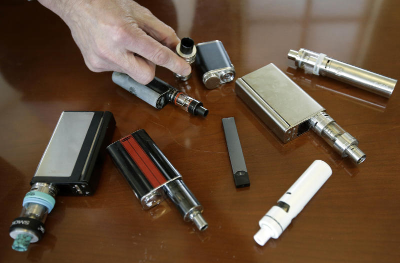 FILE - In this Tuesday, April 10, 2018 file photo, Marshfield High School Principal Robert Keuther displays vaping devices that were confiscated from students in such places as restrooms or hallways at the school in Marshfield, Mass. Massachusetts Gov. Charlie Baker is declaring a public health emergency and ordering a four-month temporary ban on all vaping products in the state. The Republican governor made the announcement Tuesday, Sept. 24, 2019, amid growing concern about the health effects of vaping products. (AP Photo/Steven Senne, File)