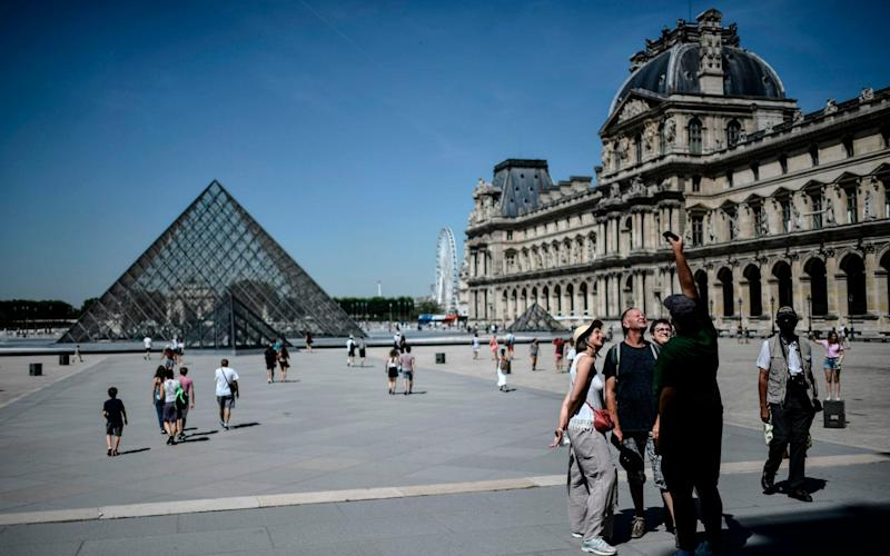 Tourists at the Louvre in Paris - STEPHANE DE SAKUTIN/AFP via Getty Images