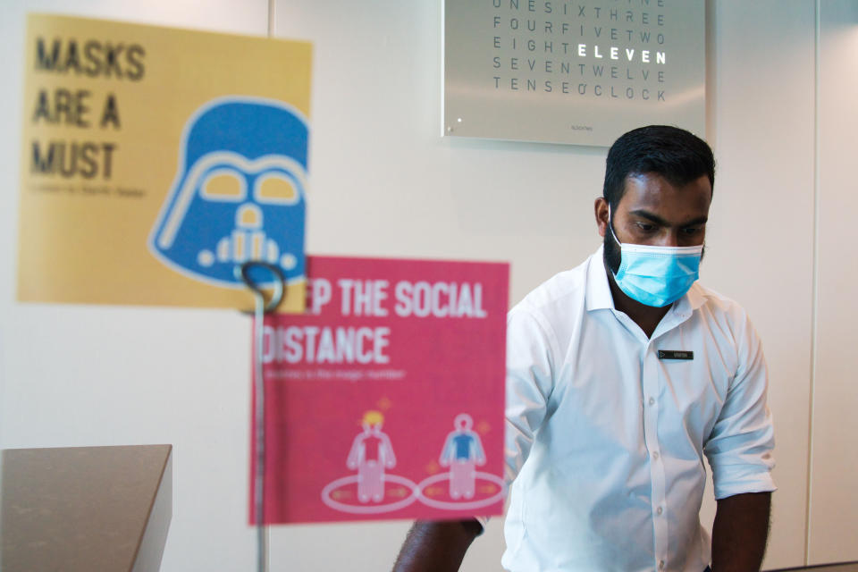 In this Monday, July 6, 2020 photograph, a front desk employee wearing a mask due to the coronavirus pandemic works on his computer at the Rove City Centre Hotel in Dubai, United Arab Emirates, Monday, July 6, 2020. Dubai reopened for tourists Tuesday amid the coronavirus pandemic, hoping to reinvigorate a vital industry for this city-state before its crucial winter tourist season. (AP Photo/Jon Gambrell)
