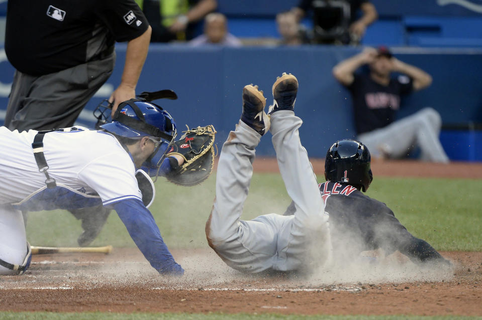 Cleveland Indians left fielder Greg Allen (1) is safe at home as Toronto Blue Jays catcher Danny Jansen (9) is late on the tag during the fifth inning of a baseball game, Wednesday, July 24, 2019 in Toronto. (Nathan Denette/Canadian Press via AP)