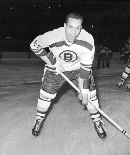 FILE - In this November 23, 1960 file photo, 25-year-old left wing Willie O'Ree, the first black player of the National Hockey League, warms up in his Boston Bruins uniform, prior to the game with the New York Rangers, at New York's Madison Square Garden. (AP Photo, File)