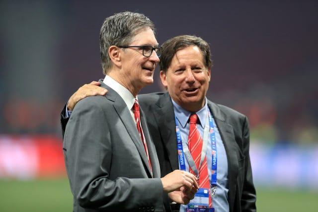 Fenway Sports Group's principal owner John W Henry and Liverpool chairman Tom Werner embrace on the pitch