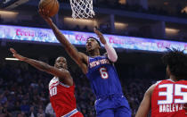New York Knicks guard Elfrid Payton, center, goes to the basket between Sacramento Kings' Harrison Barnes, left, and Marvin Bagley III, right, during the first quarter of an NBA basketball game in Sacramento, Calif., Friday, Dec. 13, 2019. (AP Photo/Rich Pedroncelli)