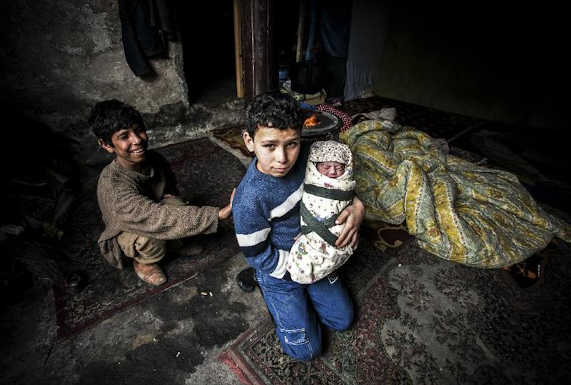 A Syrian refugee boy poses with his newborn brother as their mother lies near them in a house in the Basaksehir district of Istanbul, on March 4, 2014 (AFP Photo/Gurcan Ozturk)