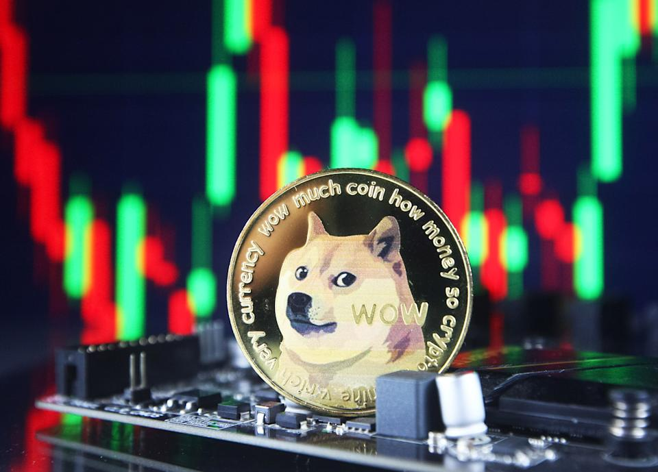 Dogecoin cryptocurrency coin and a graph are pictured in Kyiv on 08 July, 2021. (Photo by STR/NurPhoto via Getty Images)