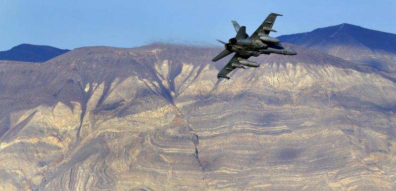 FILE - In this Feb. 27, 2017 file photo, an F/A-18D Hornet from the VX-9 Vampire squadron at Naval Air Weapons Station China Lake, flies out of what is known as Star Wars Canyon toward the Panamint range in Death Valley National Park, Calif. On Wednesday, July 31, 2019 a U.S. Navy F/A-18 Super Hornet jet crashed Wednesday in the California desert and a search-and-rescue operation was underway, officials said. The single-seat warplane went down at 9:50 a.m. during a routine training mission north of the China Lake base. (AP Photo/Ben Margot, File)