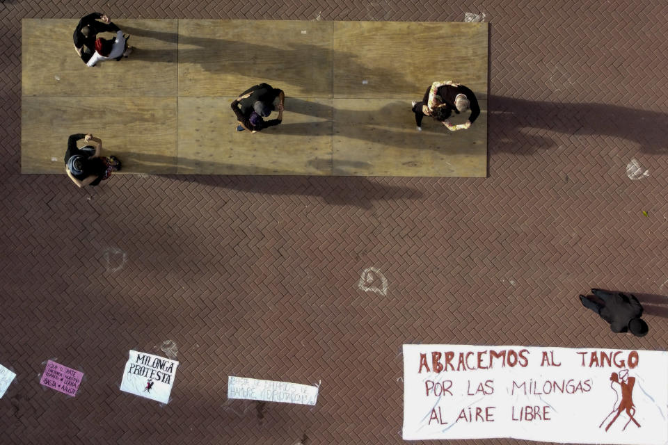 """FILE - In this May 29, 2021 file photo, couples dance tango in protest to demand to be allowed to dance in open spaces during the COVID-19 pandemic lockdown in Buenos Aires, Argentina. The sign at right reads in Spanish """"We embrace tango. For outdoor milongas,"""" referring to the music genre. (AP Photo/Natacha Pisarenko, File)"""