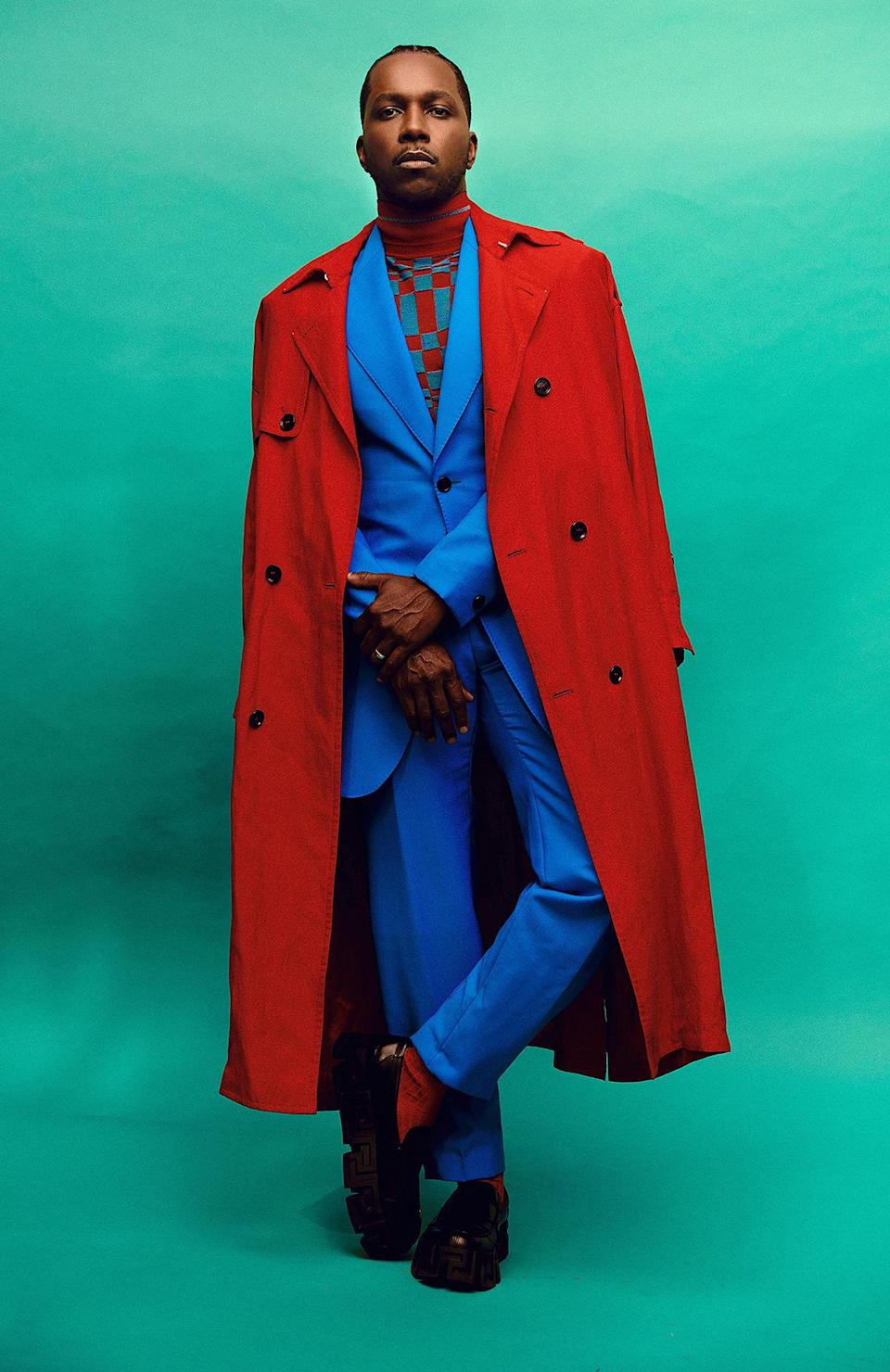 <p>brings the color in a bright blue suit with red trench coat and checkerboard knit top, all by Versace. </p>