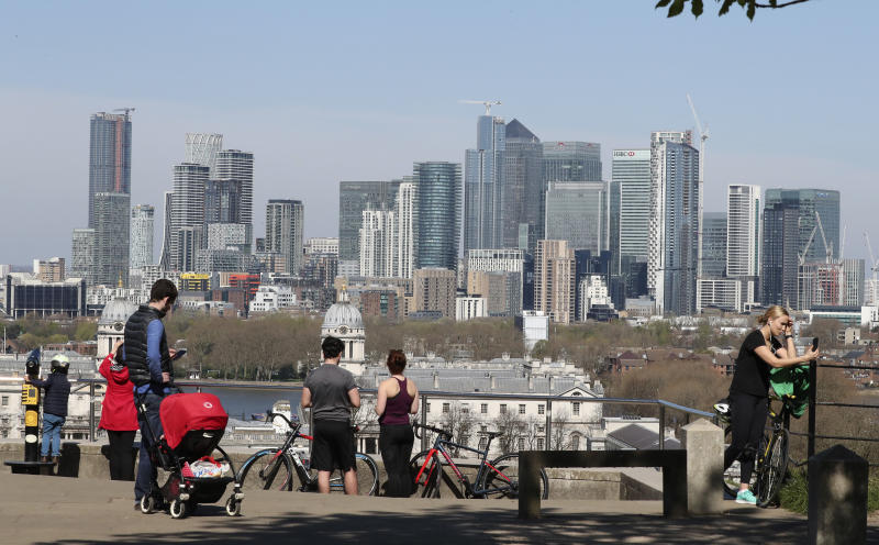 People stand on the upper section of Greenwich Park overlooking the Canary Wharf skyline, as another London park closed yesterday with most parks remaining open with the warning that they will close if people fail to observe the British government guidelines to help stop the spread of coronavirus, Sunday, April 5, 2020. The new coronavirus causes mild or moderate symptoms for most people, but for some, especially older adults and people with existing health problems, it can cause more severe illness or death. (AP Photo/Tony Hicks)