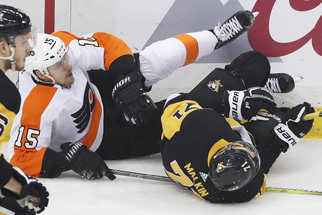 Pittsburgh Penguins' Evgeni Malkin (71) and Philadelphia Flyers' Jori Lehtera (15) collide and slide into the boards during the first period in Game 5 of an NHL first-round hockey playoff series in Pittsburgh, Friday, April 20, 2018. Malkin went to the locker room following the collision. (AP Photo/Gene J. Puskar)