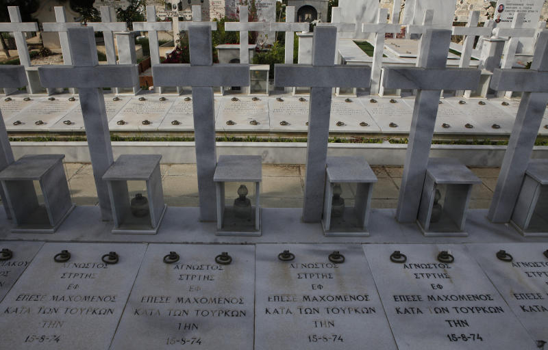 """Graves of persons killed during the 1974 Turkish invasion of Cyprus, while the words in Greek read """"unknown soldier"""" fell in battle against the Turks"""", at Lakatamia military cemetery in the Cypriot capital Nicosia, Thursday, Nov. 29, 2012. A Cyprus court has ordered the government to pay Euro 324,000 ($419,668 approx) in damages to the wife and two daughters of a soldier who was killed during Turkey's 1974 invasion of the country but who was listed as missing in action for more than two decades. (AP Photo/Petros Karadjias)"""