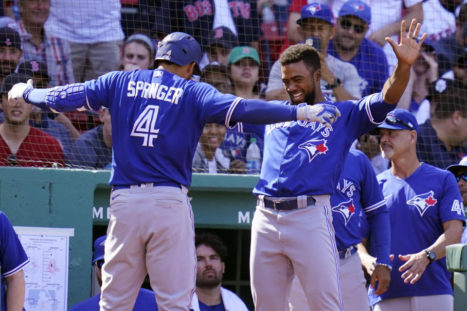 Toronto Blue Jays' George Springer (4) celebrates with Teoscar Hernandez, right, after his solo home run off Boston Red Sox starting pitcher Garrett Richards during the fifth inning of a baseball game at Fenway Park, Wednesday, July 28, 2021, in Boston. (AP Photo/Charles Krupa)