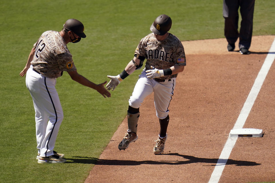 San Diego Padres' Jake Cronenworth, right, is greeted by third base coach Bobby Dickerson after hitting a home run during the fourth inning of a baseball game against the Los Angeles Dodgers, Sunday, April 18, 2021, in San Diego. (AP Photo/Gregory Bull)