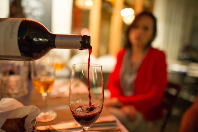 Red wine is poured into a glass at an outdoor Zurich restaurant.