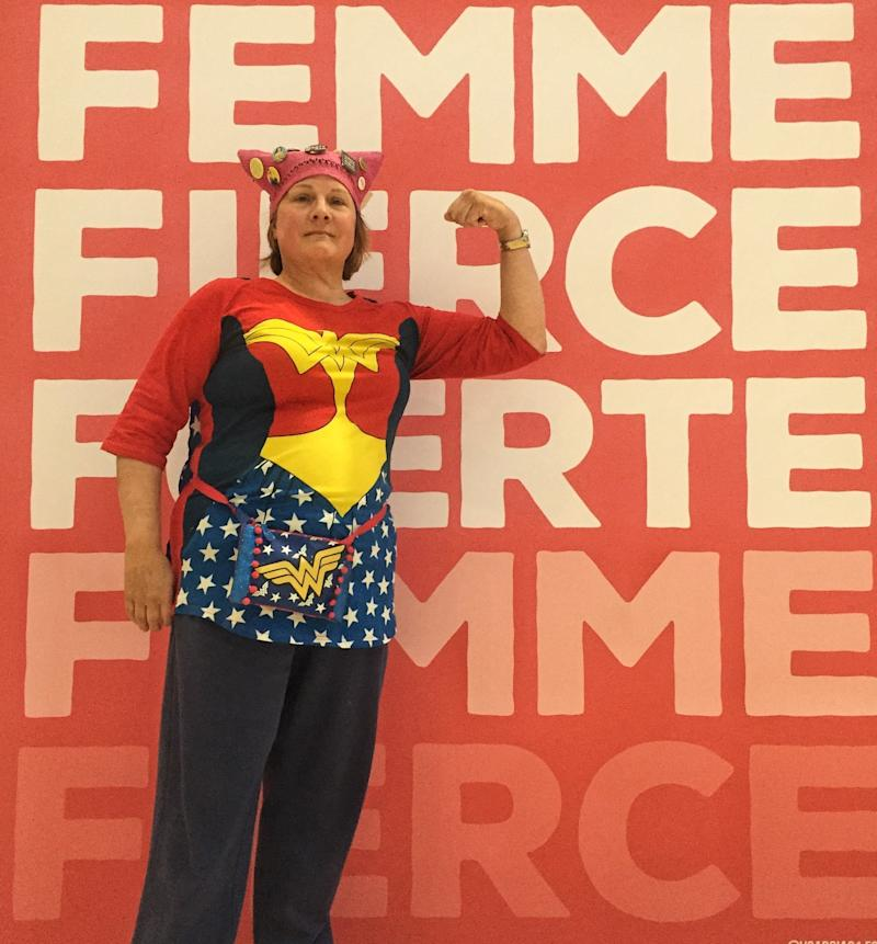 "Karen Dunnam, 60, posed in front of a poster at the Women's Convention wearing her fall ""pussy hat."" (Catherine Pearson/HuffPost)"