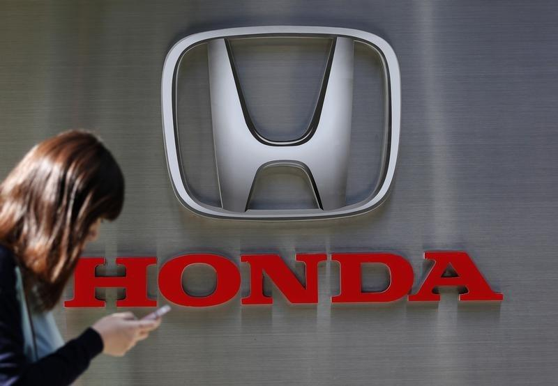 A woman using her mobile phone walks past a logo of Honda Motor Co outside the company's dealership in Tokyo