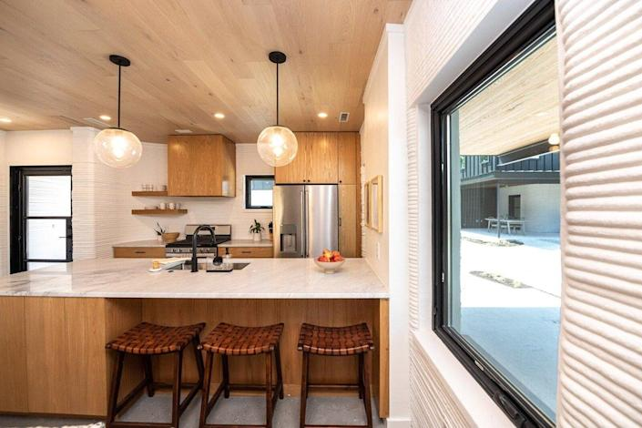 The interiors of the new 3D printed homes are defined by textured walls, wood accents, and plenty of modern amenities.