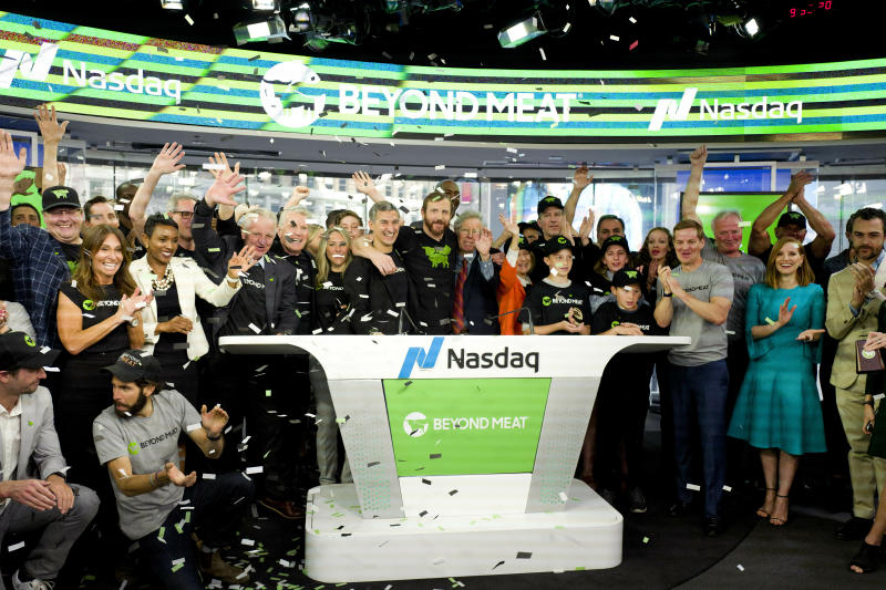 Ethan Brown, center, CEO of Beyond Meat, attends the Opening Bell ceremony with guests to celebrate the company's IPO at Nasdaq, Thursday, May 2, 2019 in New York. California-based Beyond Meat makes burgers and sausages out of pea protein and other ingredients. (AP Photo/Mark Lennihan).