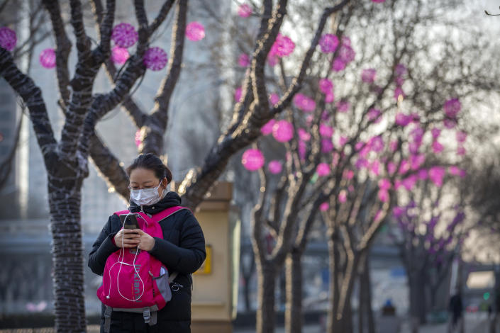 A woman wears a face mask as she walks along a street in Beijing, Wednesday, Jan. 29, 2020. China as of Wednesday has more infections of a new virus than it did in with SARS, though the death toll is still lower. (AP Photo/Mark Schiefelbein)